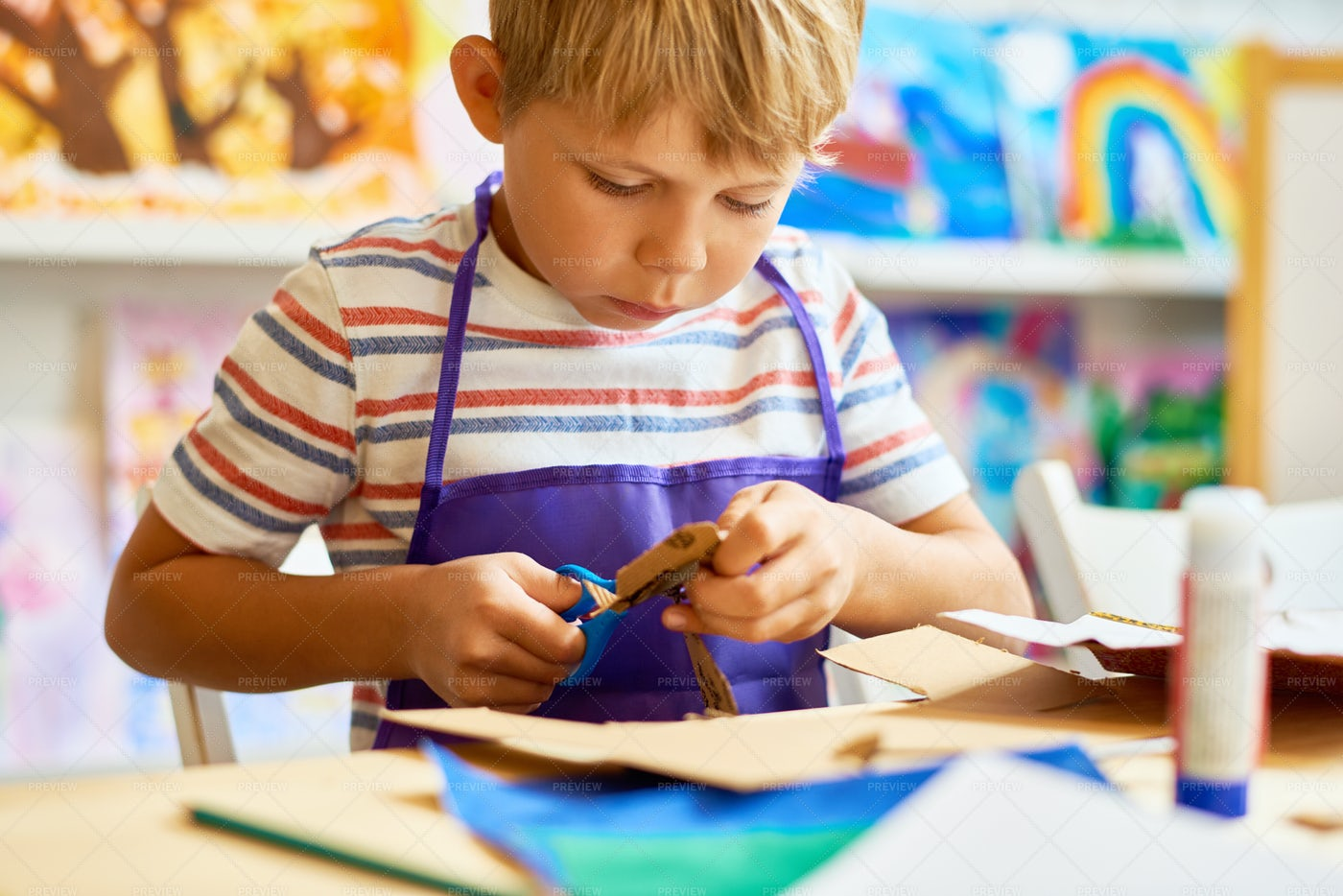 Little Boy Cutting Paper In Craft...: Stock Photos