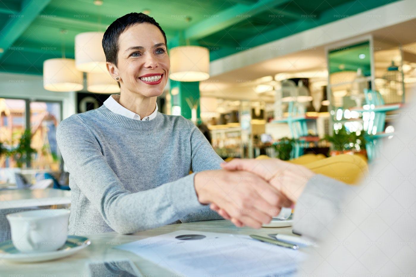 Businesswomen Shaking Hands In Cafe...: Stock Photos