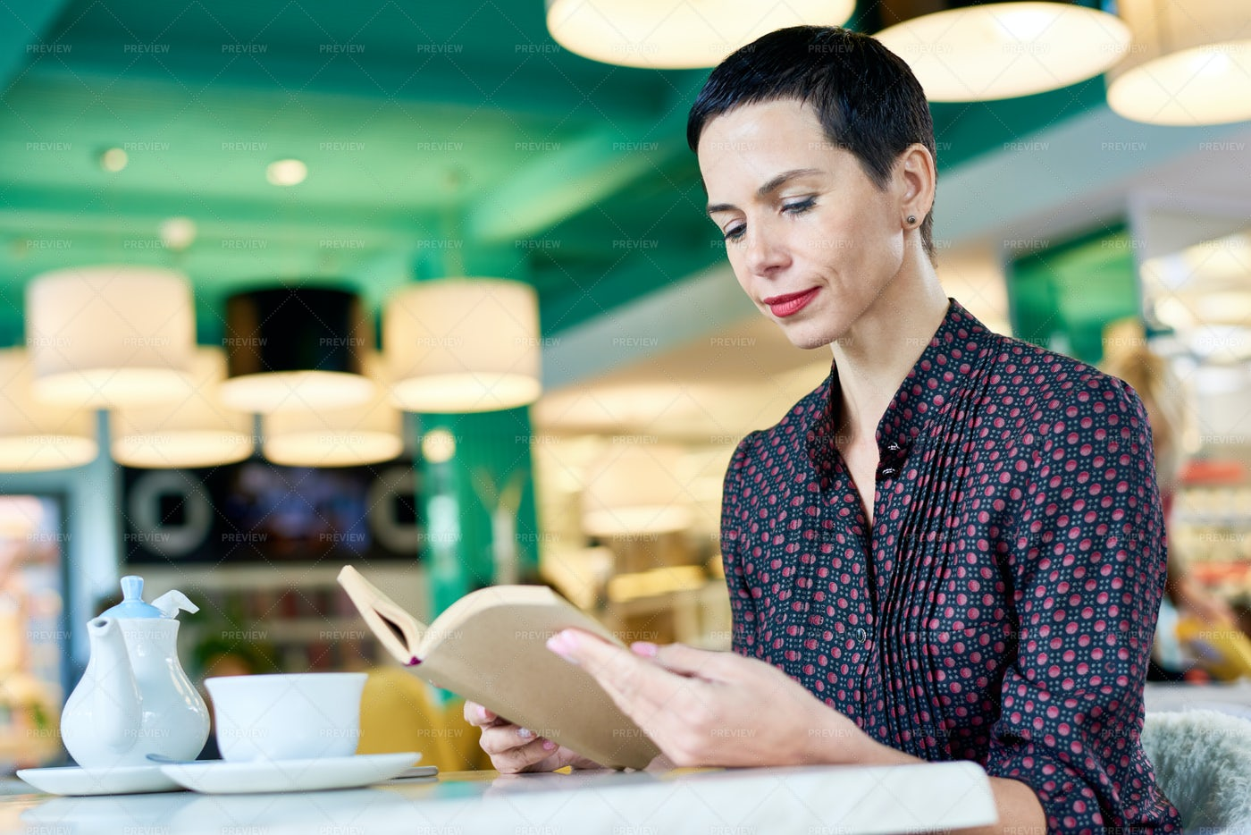 Elegant Woman Reading Book In Cafe: Stock Photos