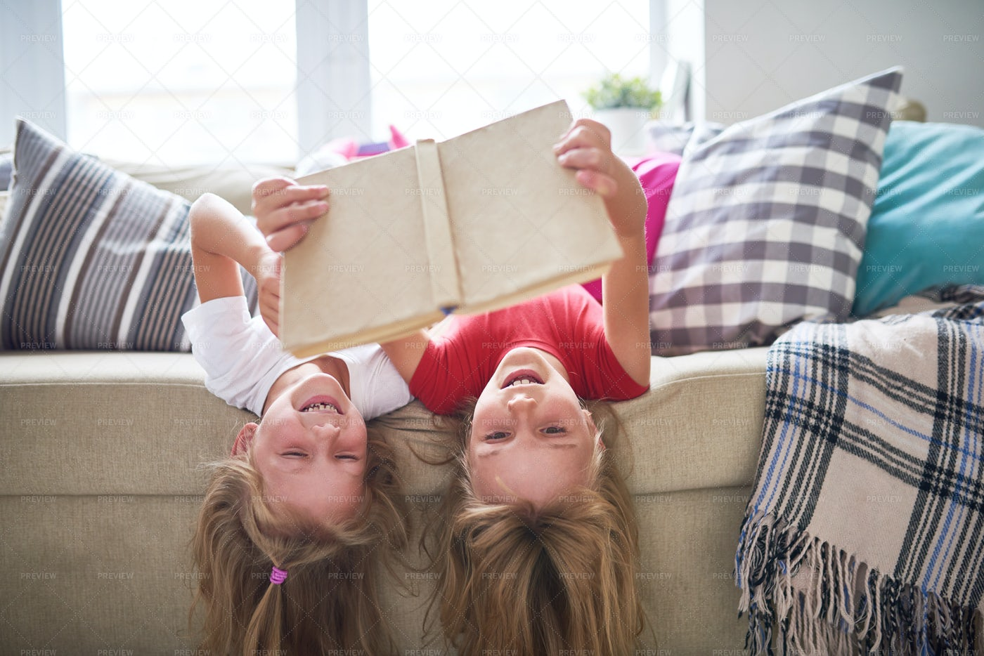 Sisters Reading Book Upside Down: Stock Photos