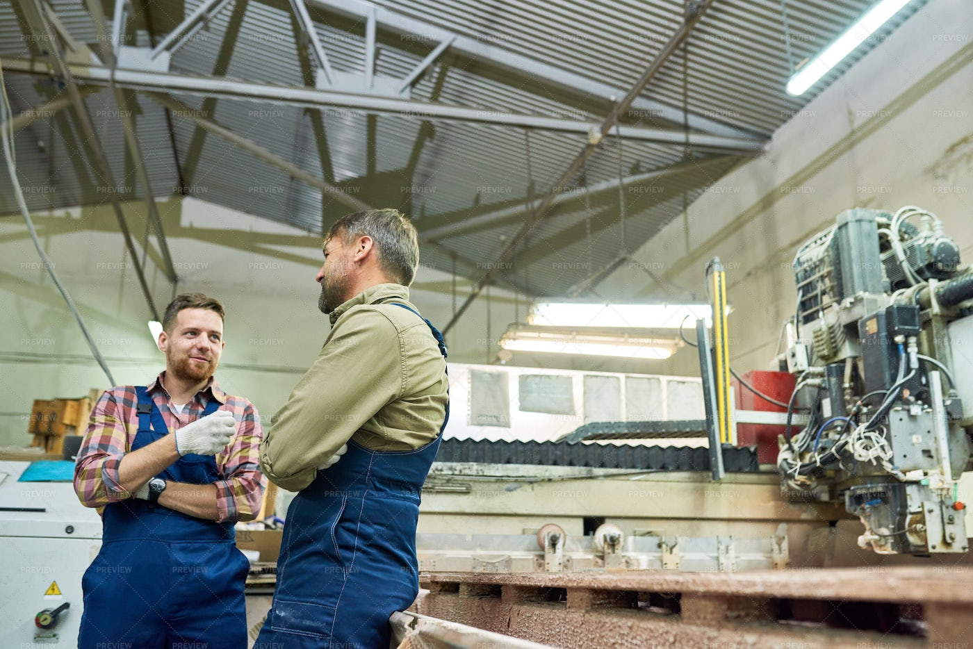 Two Factory Workers Chatting In...: Stock Photos