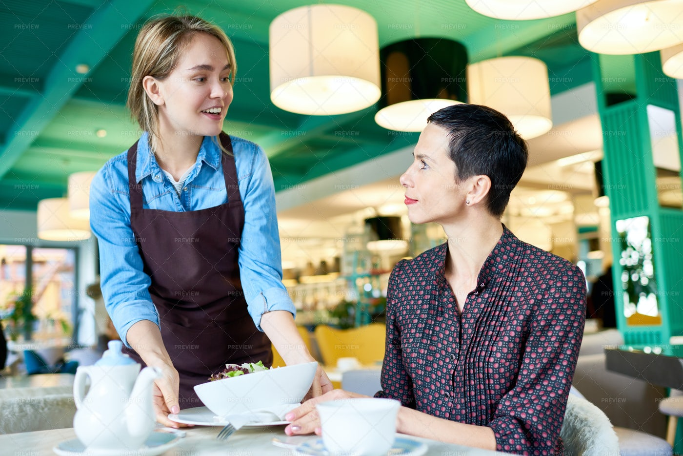 Young Waitress Bringing Food To...: Stock Photos