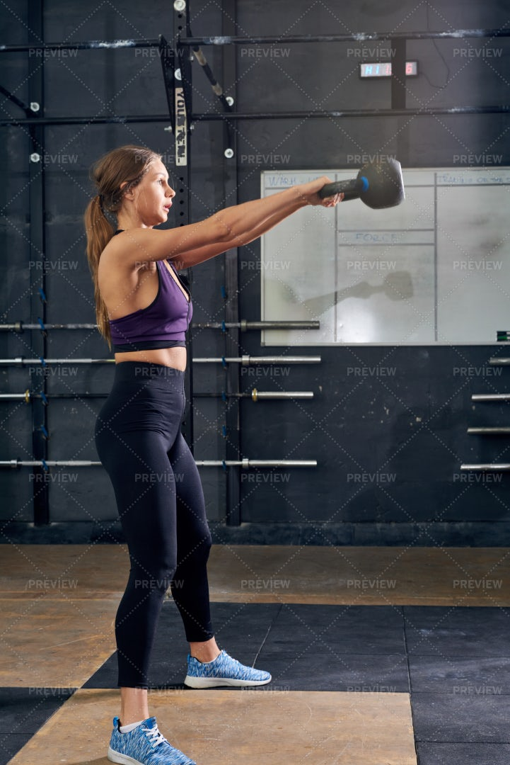 Young Woman Swinging Kettlebell In...: Stock Photos