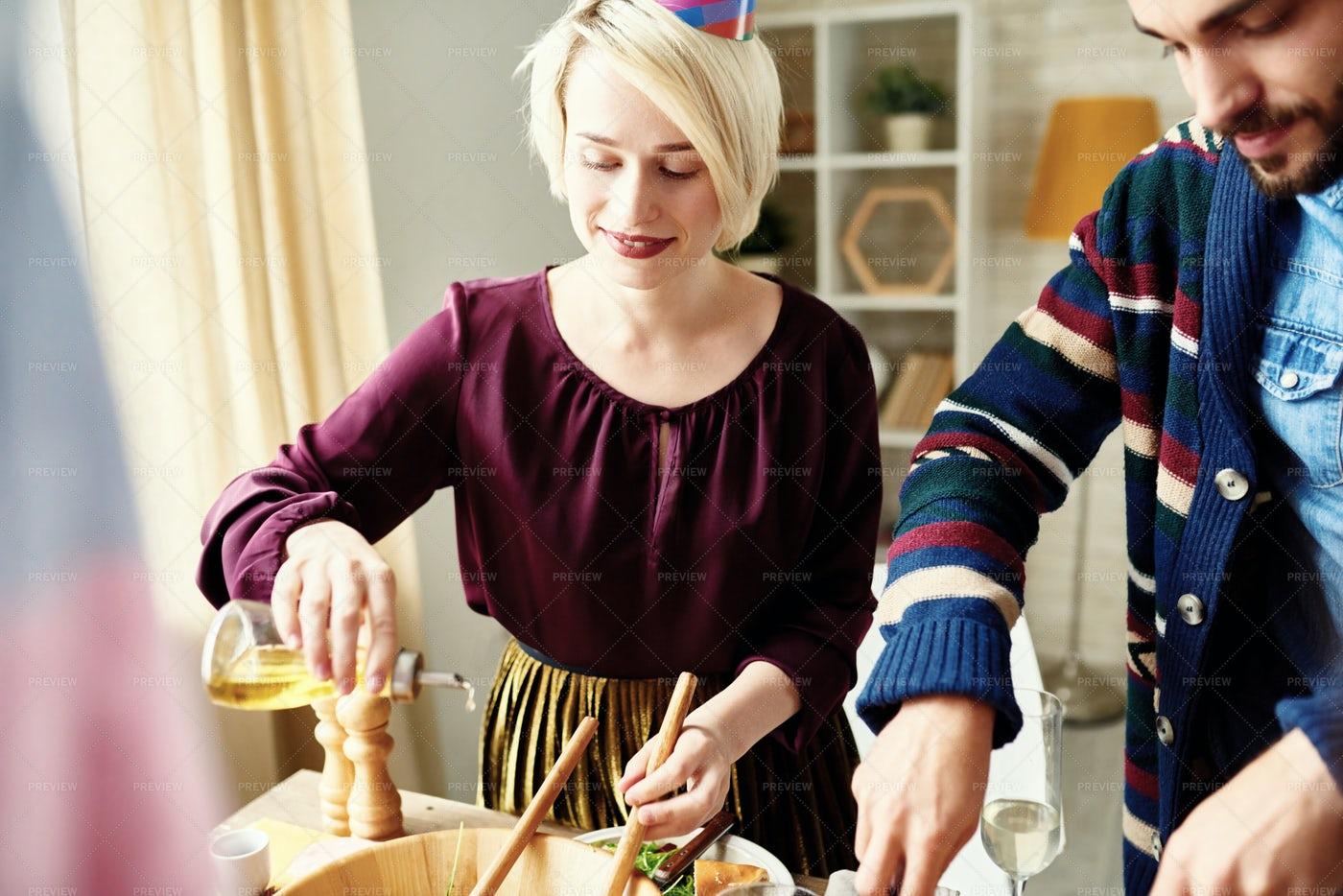 Young Woman Making Salad At Party: Stock Photos