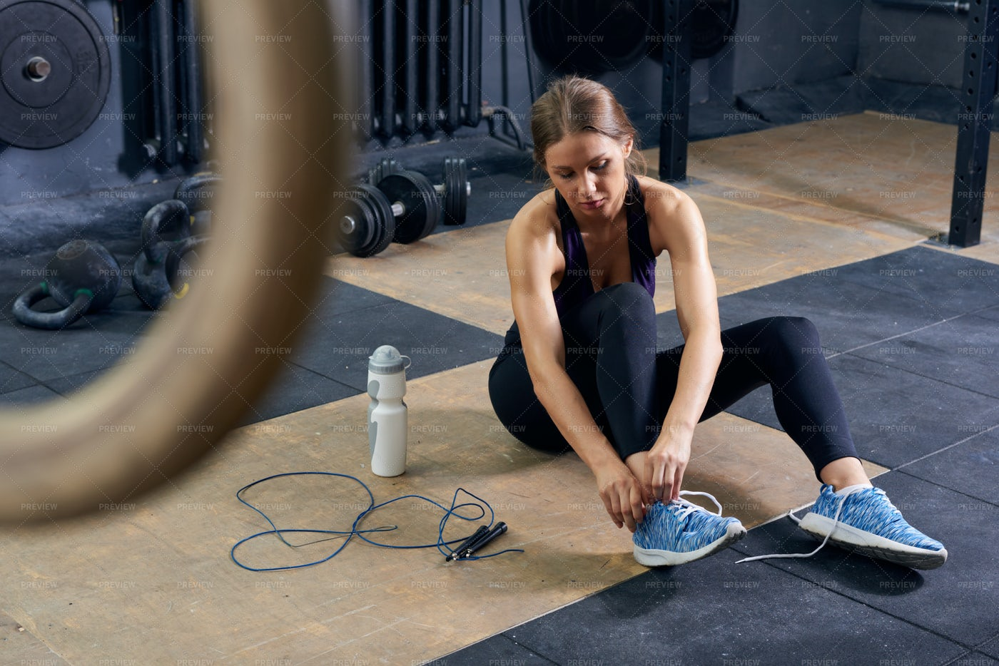 Young Woman Tying Shoes In Gym: Stock Photos