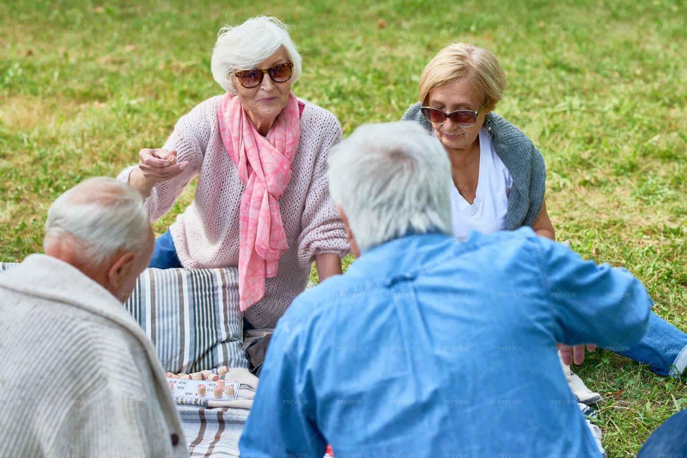 Seniors Enjoying Picnic In Park: Stock Photos