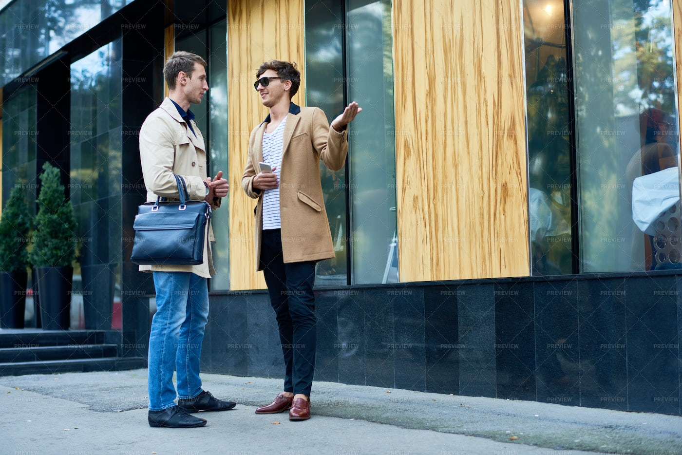 Two Stylish Men Chatting Outdoors: Stock Photos