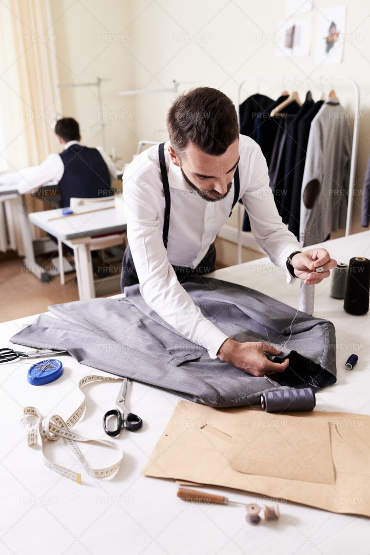 Young Tailor Wrapped Up In Work: Stock Photos