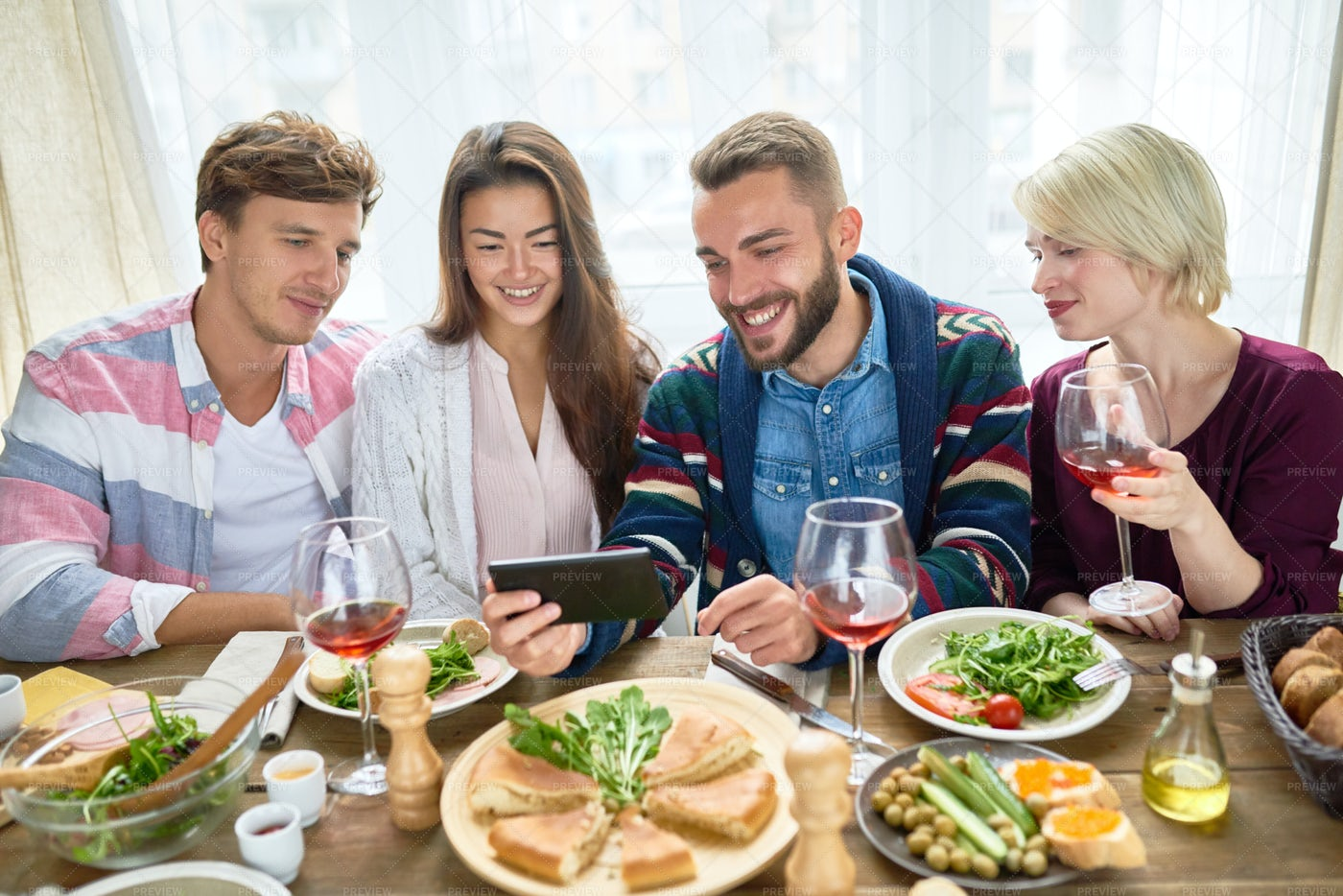 Friends Watching Video At Dinner...: Stock Photos