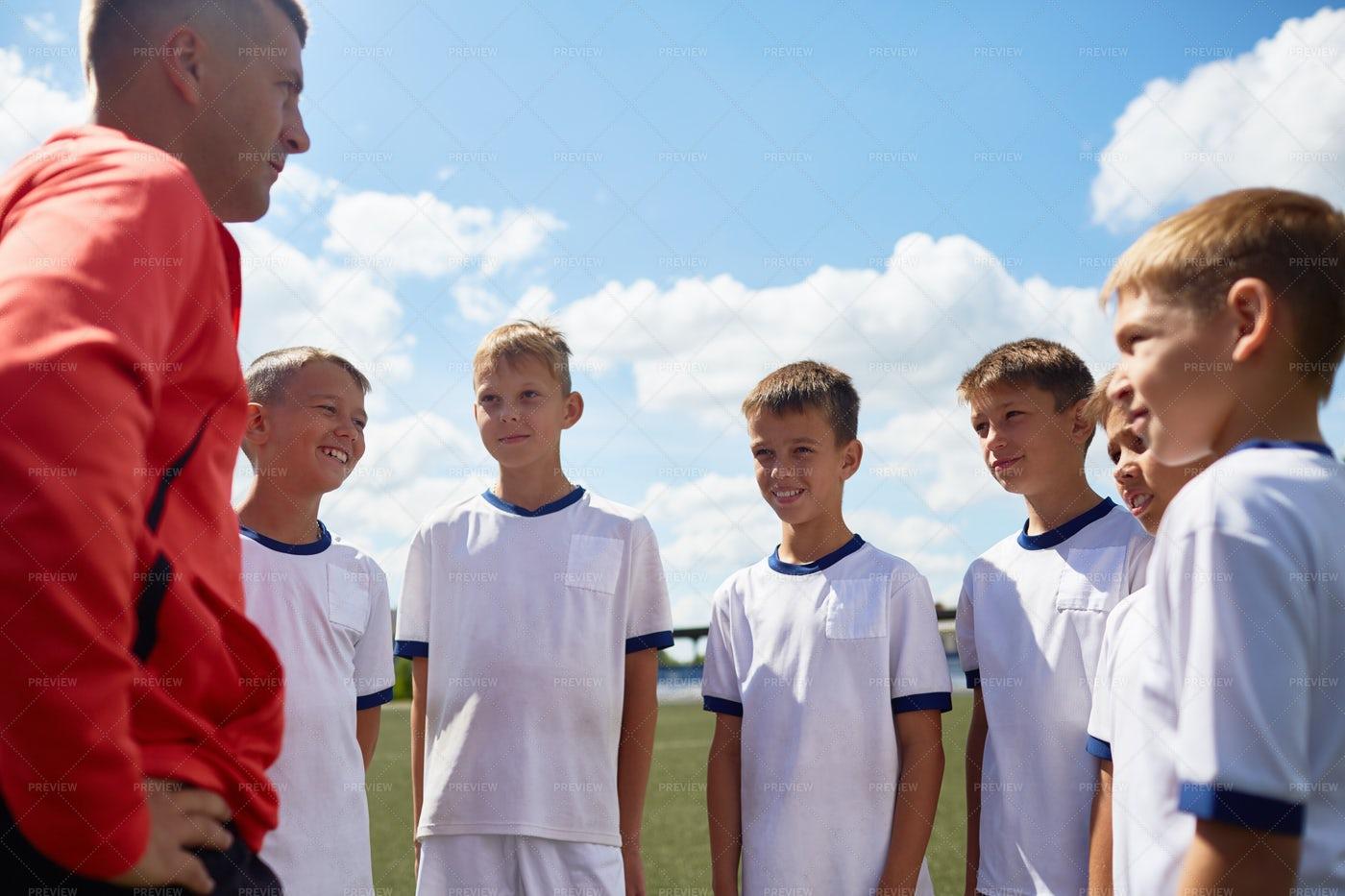 Coach Motivating Football Team: Stock Photos