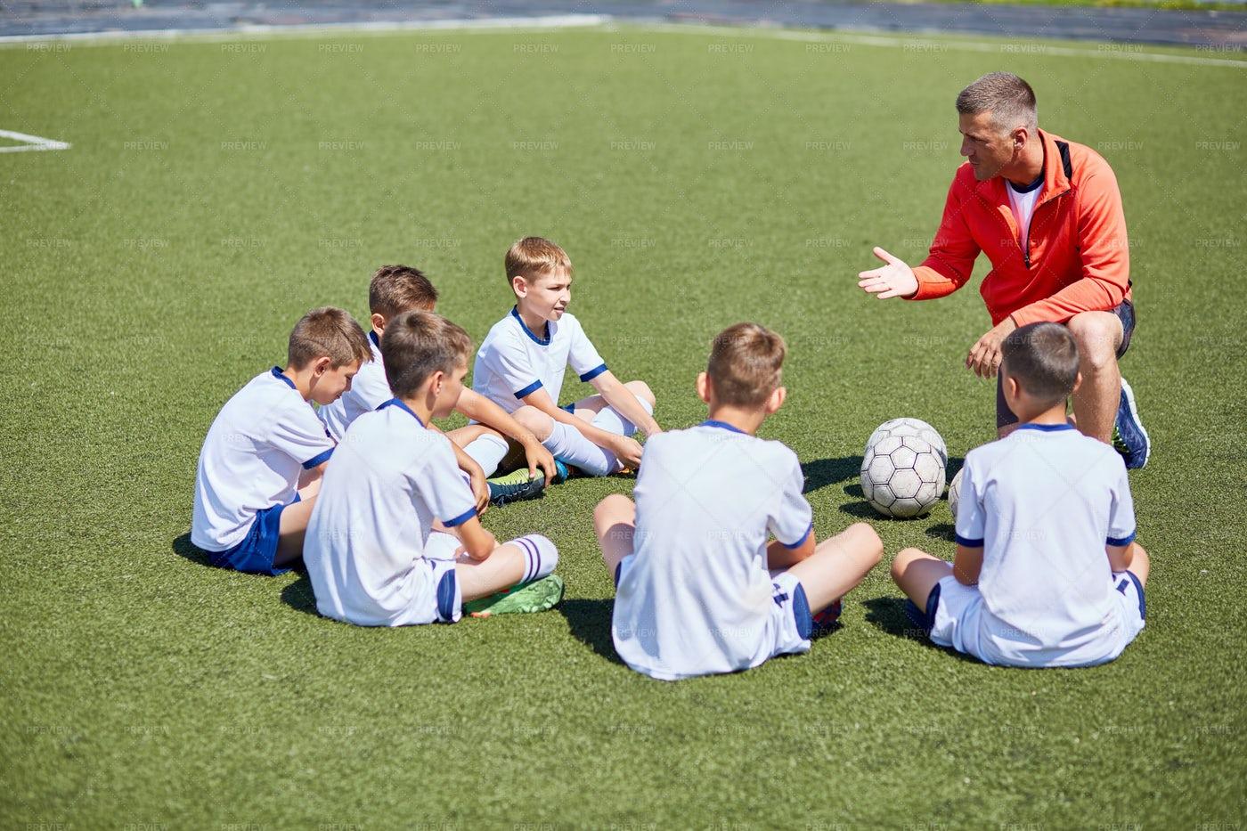 Coach Instructing  Football Team In...: Stock Photos