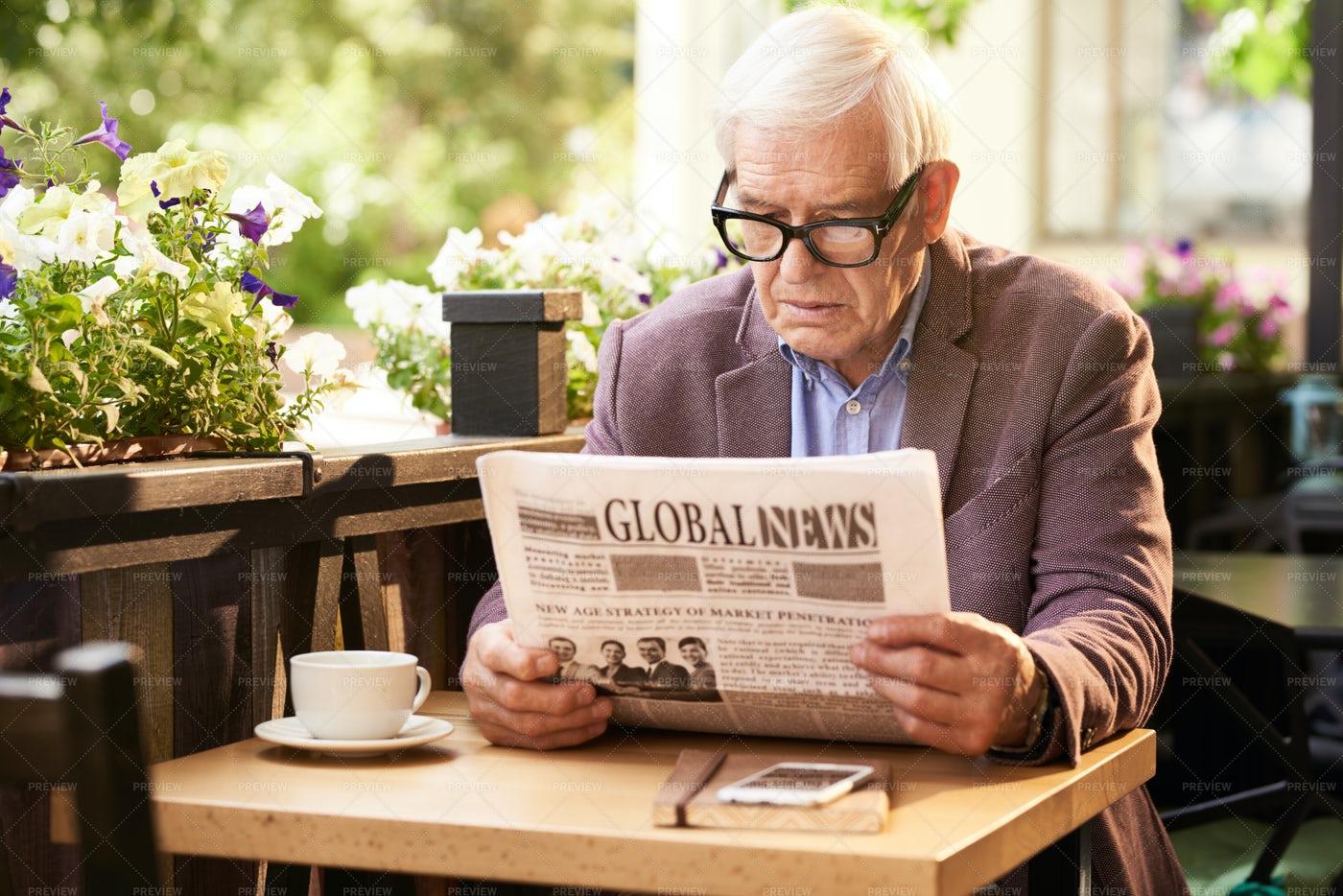 Senior Man Reading Newspaper In...: Stock Photos
