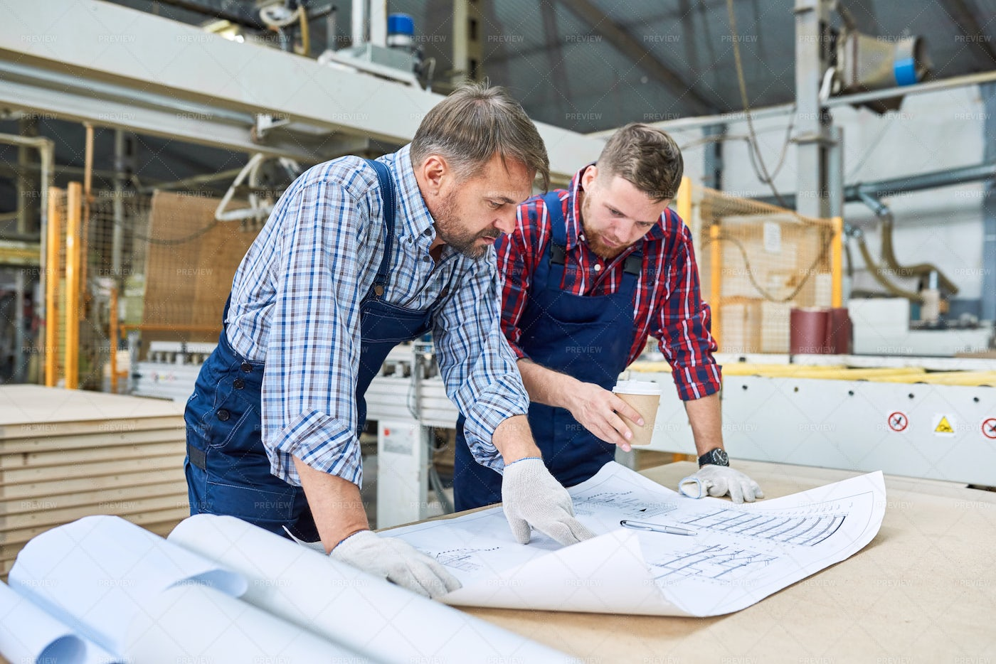 Workers Looking At Plans: Stock Photos