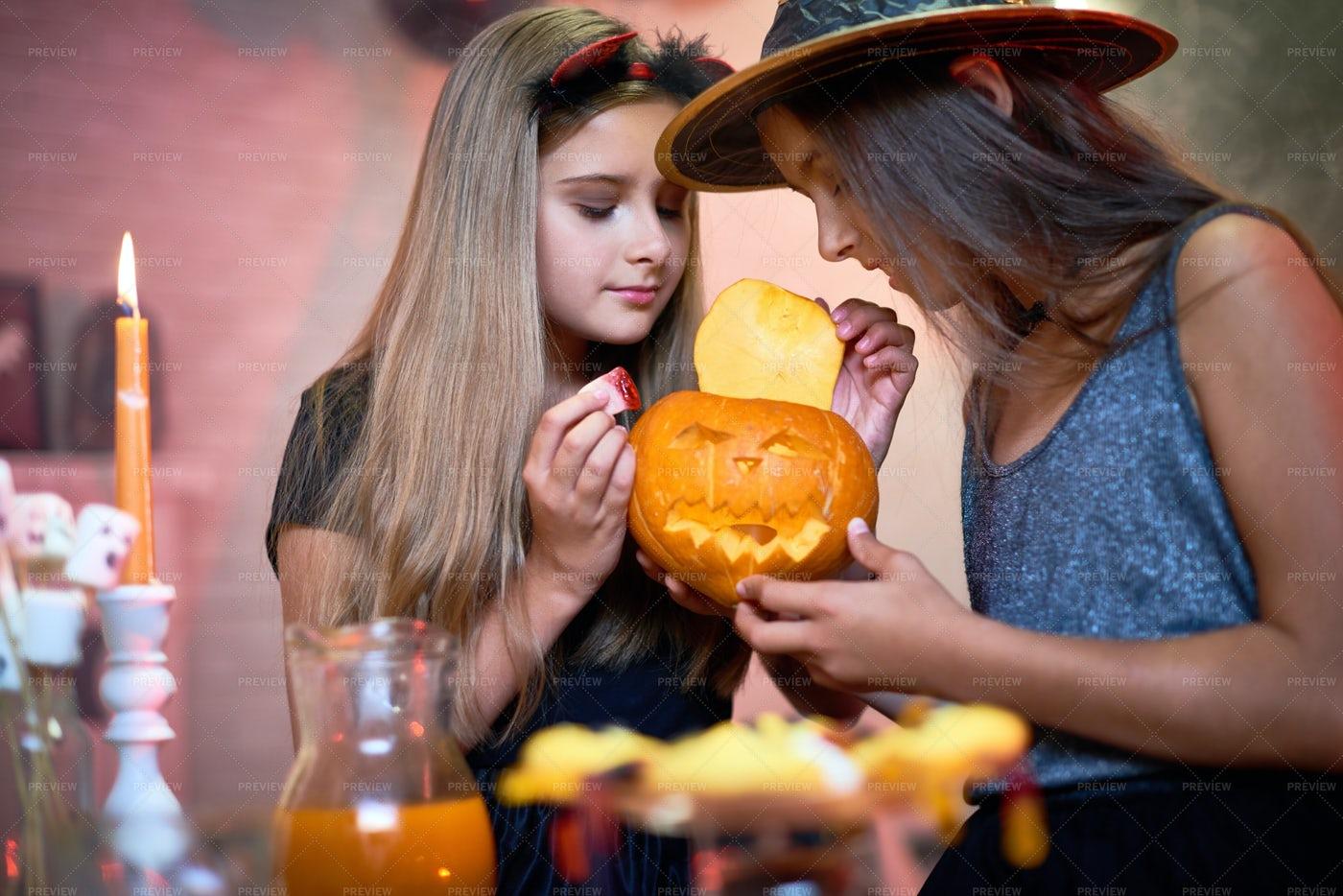 Curious Girls Making Jack-o-lantern: Stock Photos