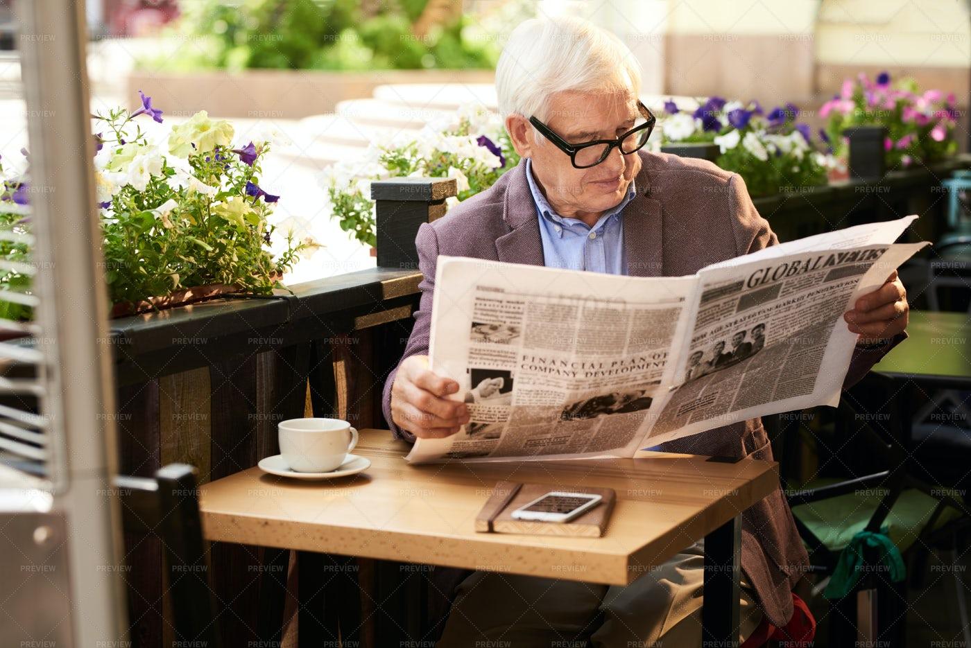 Modern Senior Man Reading Newspaper...: Stock Photos