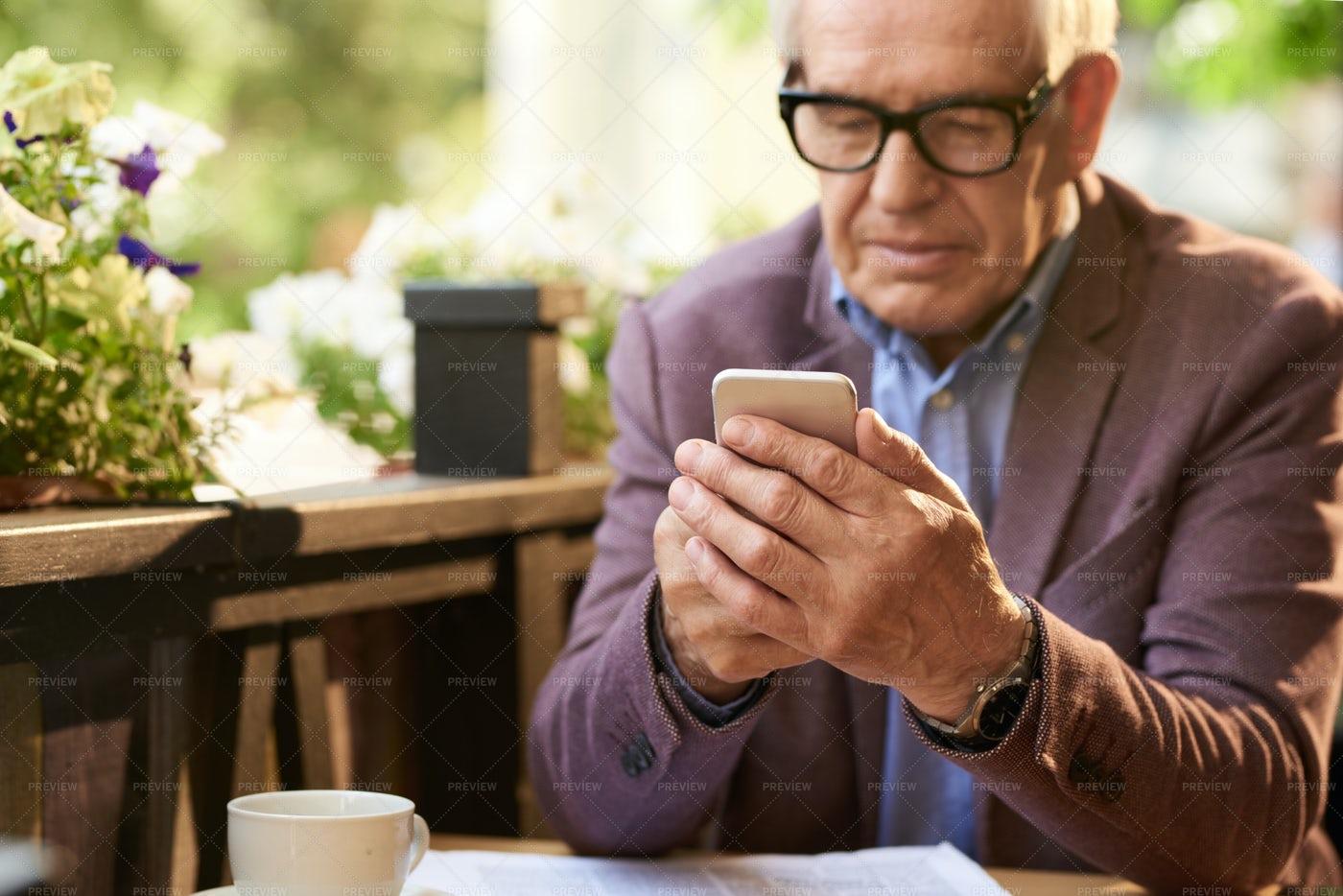 Senior Man Holding Smartphone In...: Stock Photos