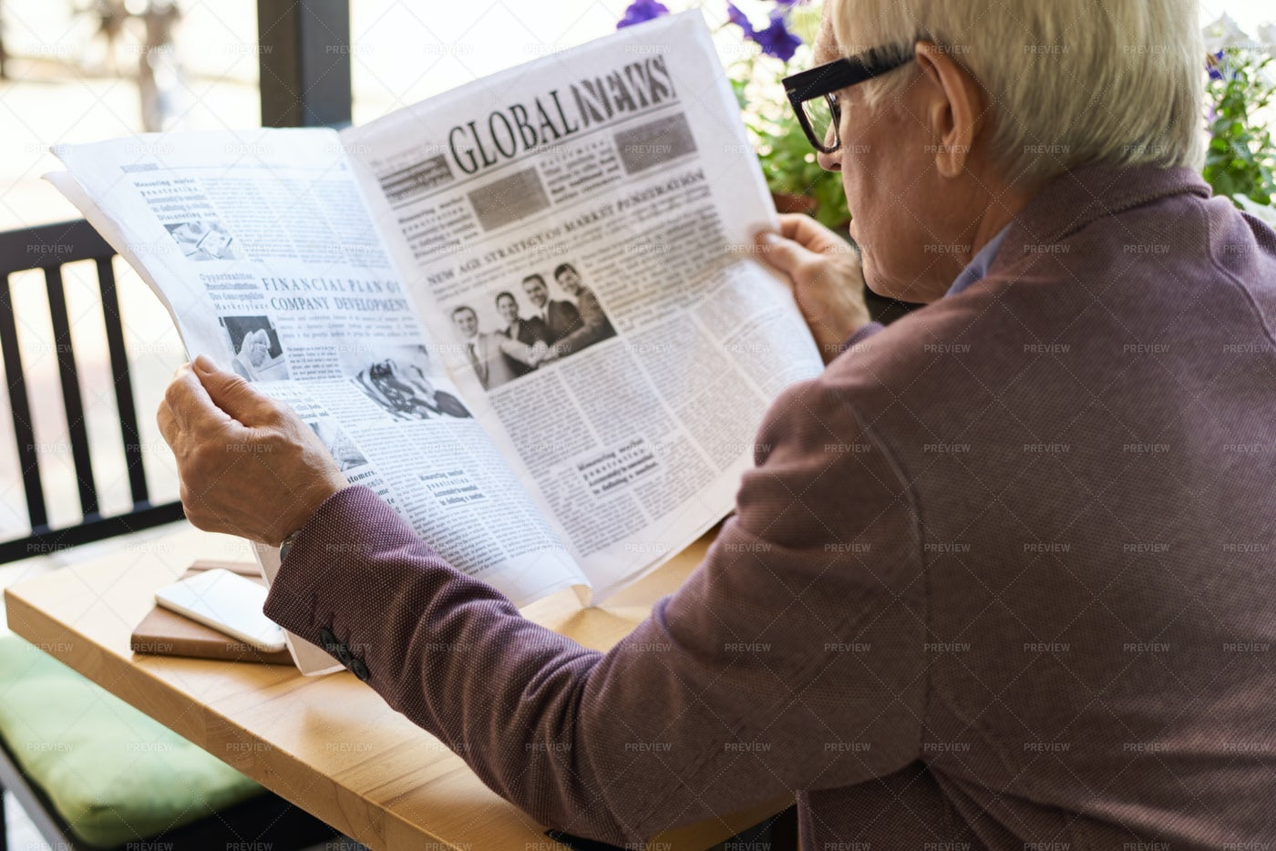 Senior Man Reading Newspaper At...: Stock Photos