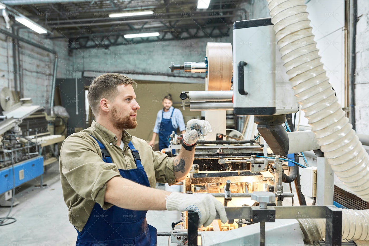 Young Worker Using  Machine At...: Stock Photos