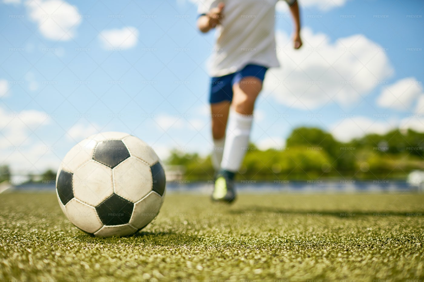 Boy Kicking Ball In Football Field: Stock Photos