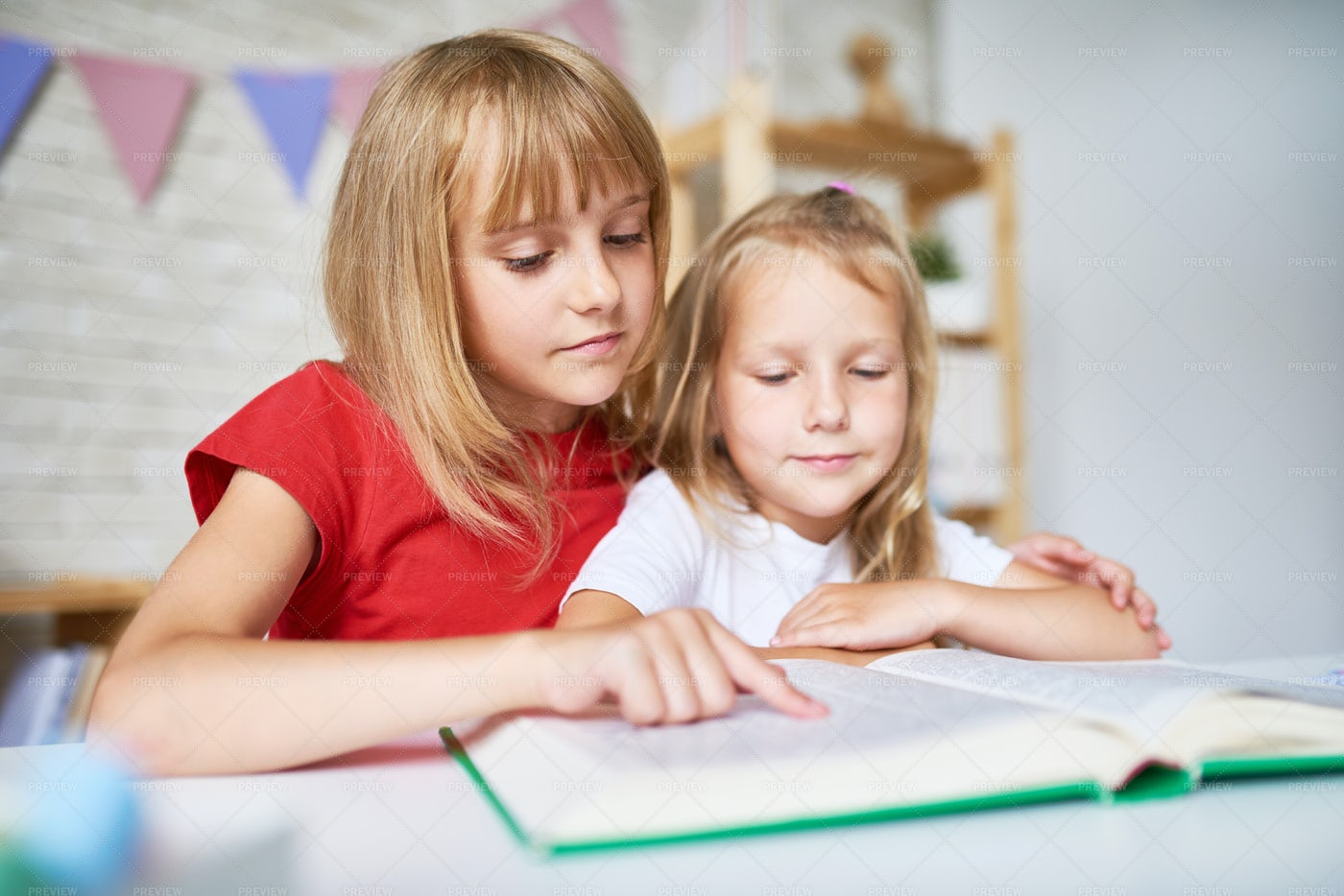 Little Sisters Focused On Reading: Stock Photos