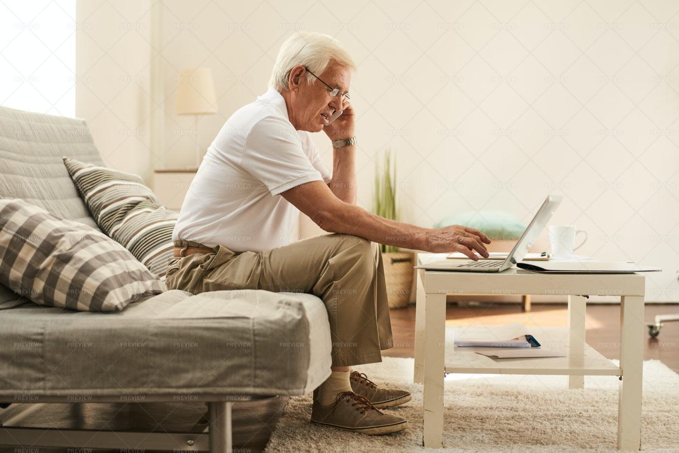 Senior Man Working In Living Room: Stock Photos