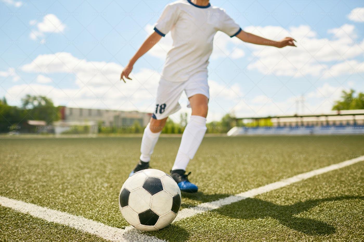 Boy In Uniform Kicking Ball On...: Stock Photos
