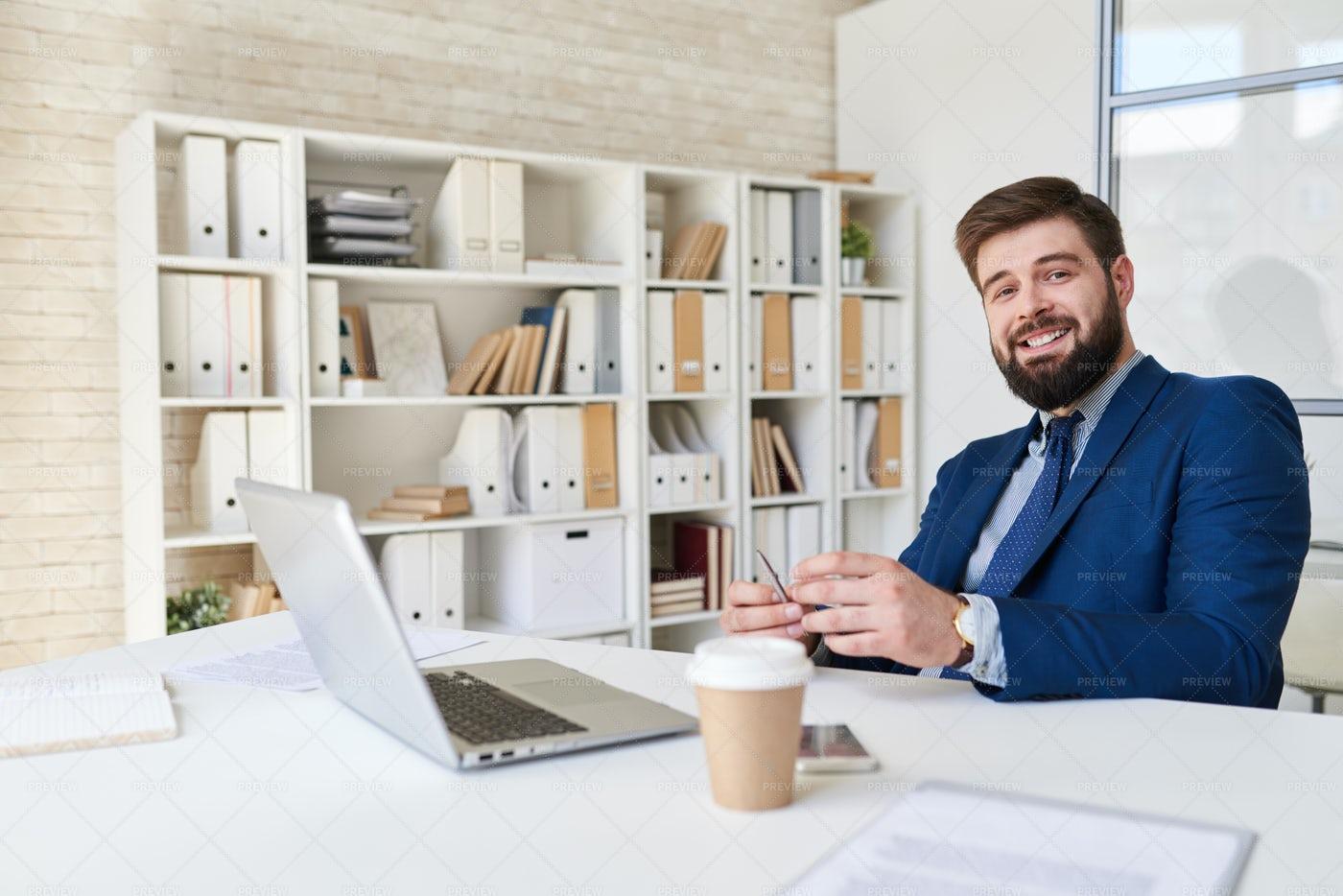 Smiling Businessman Posing At Desk...: Stock Photos