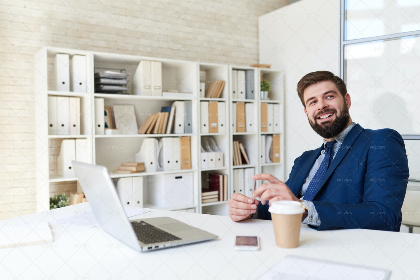 Smiling Businessman At Desk In...: Stock Photos