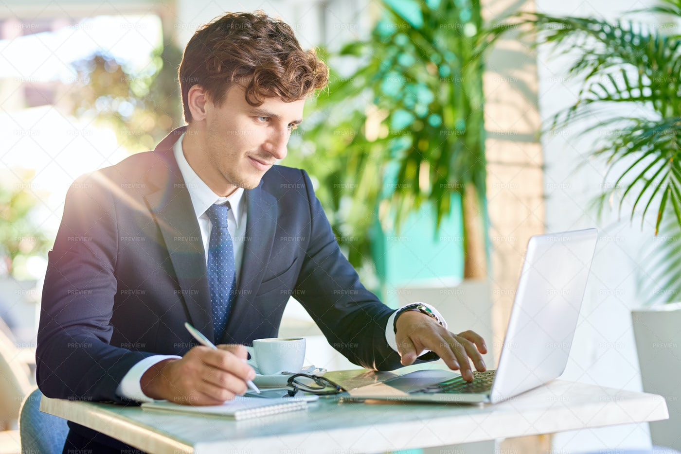 Handsome Businessman Working At...: Stock Photos