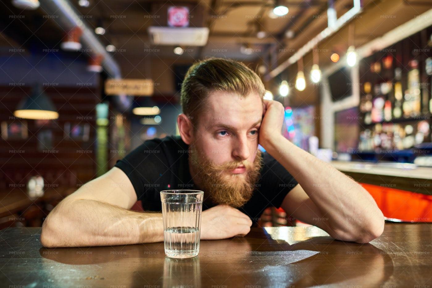 Sad Bearded Man Getting Drunk In...: Stock Photos