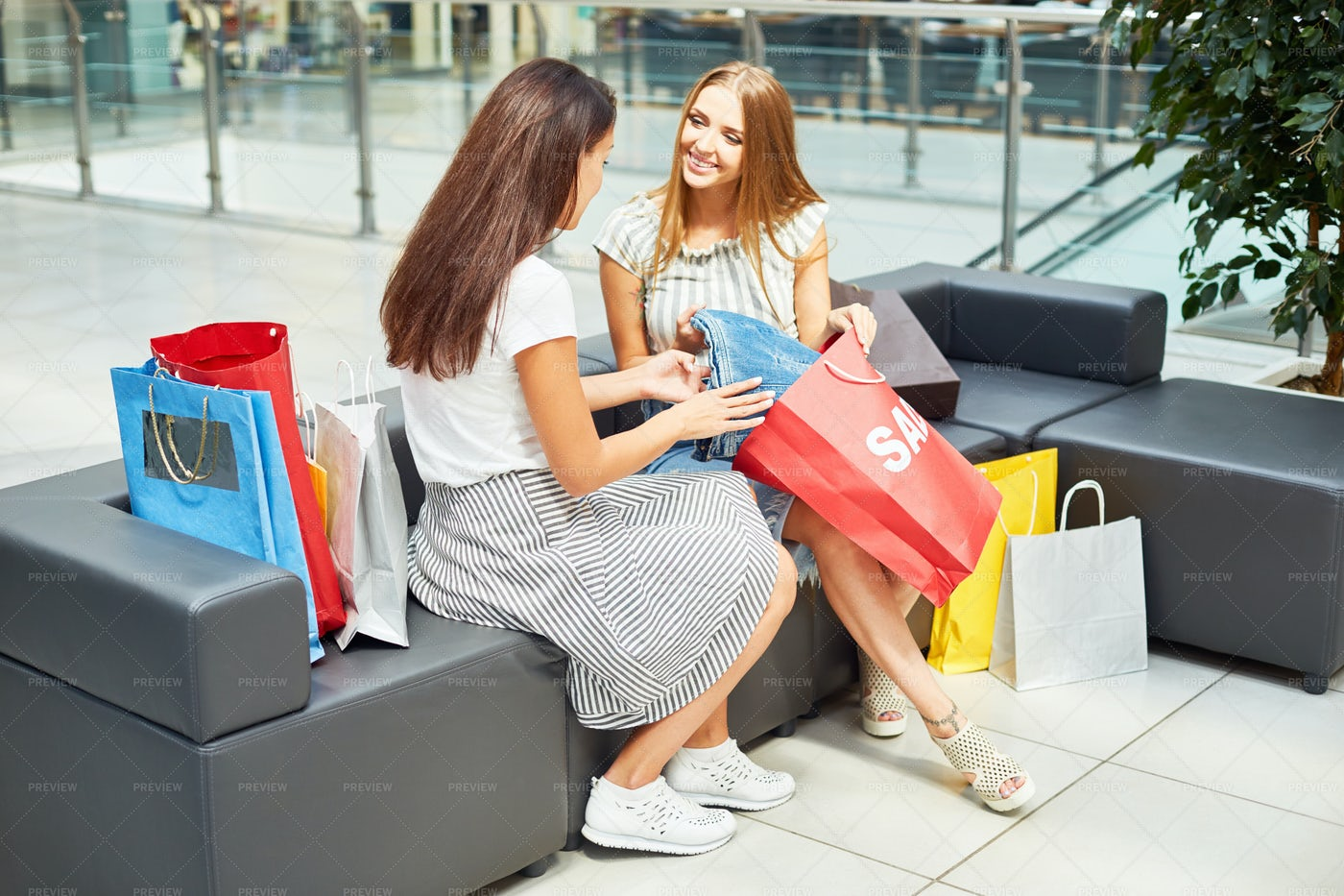 Two Young Women Discussing Sale: Stock Photos