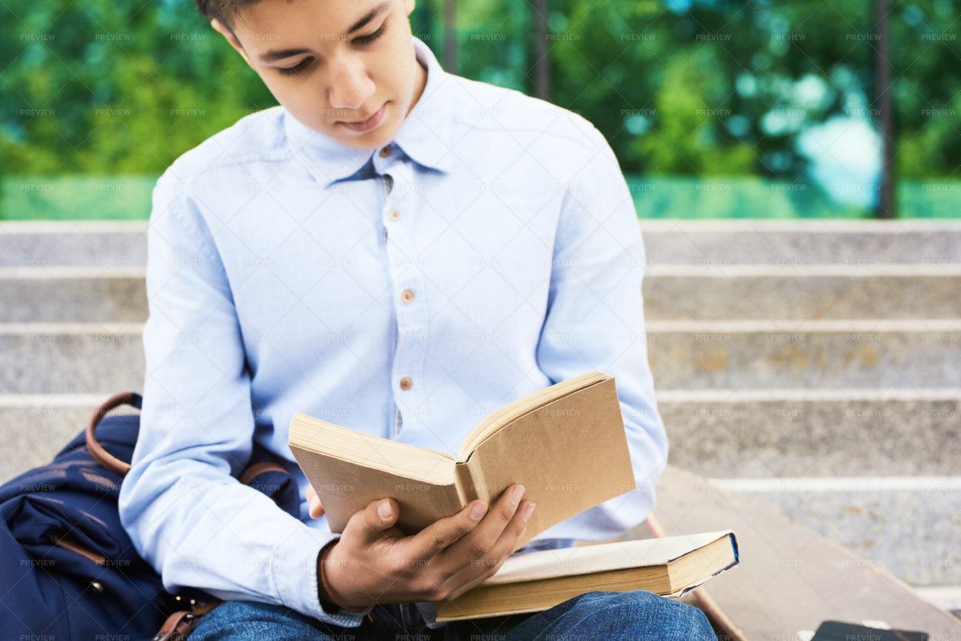 Teenage Boy Reading Books Outdoors: Stock Photos