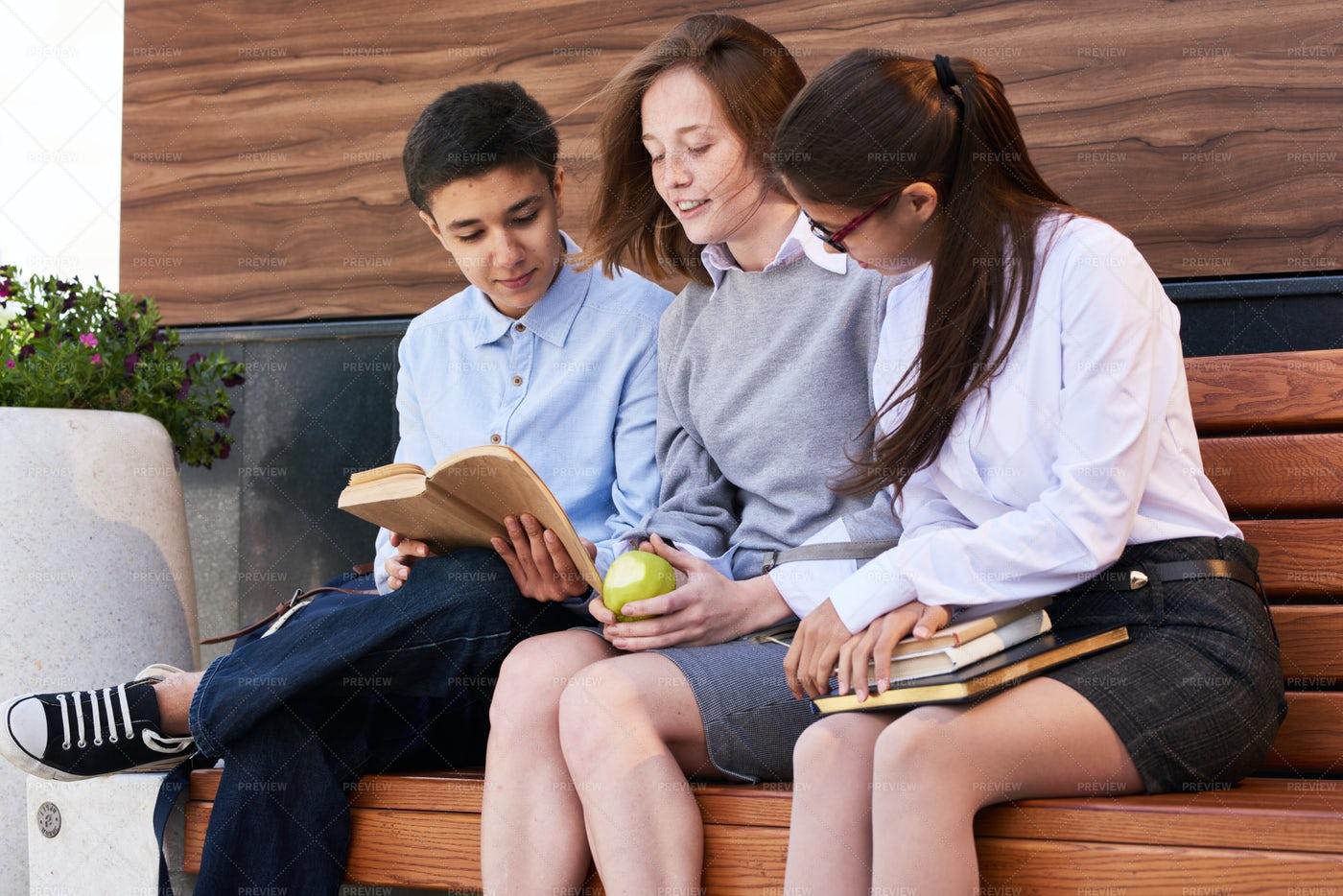 Teenage Friends Reading Textbook...: Stock Photos