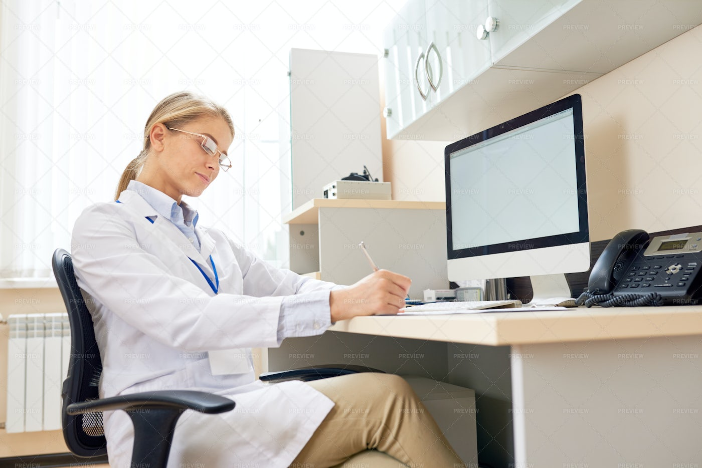 Female Doctor Working At Desk: Stock Photos