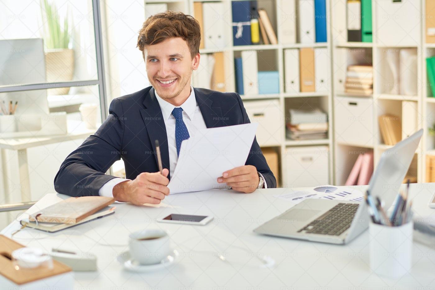 Happy Businessman Reading Documents: Stock Photos