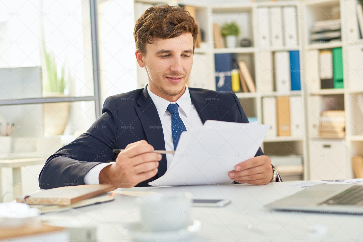 Businessman Reading Document In...: Stock Photos