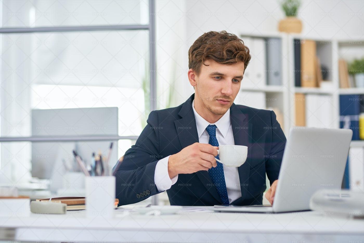 Businessman Drinking Coffee At Desk...: Stock Photos