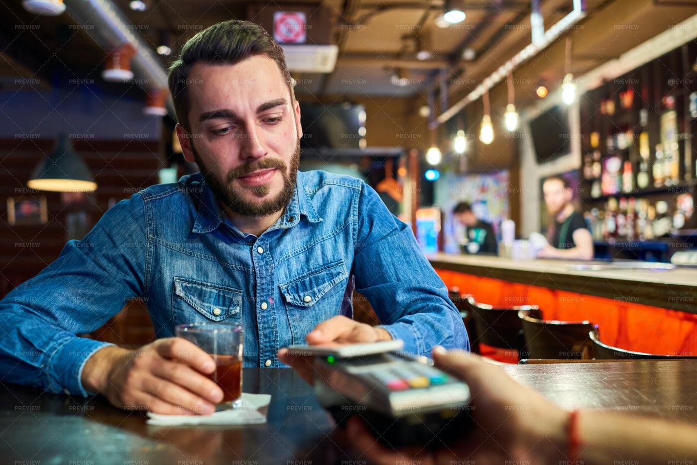 Drunk Man Paying Via NFC In Pub: Stock Photos