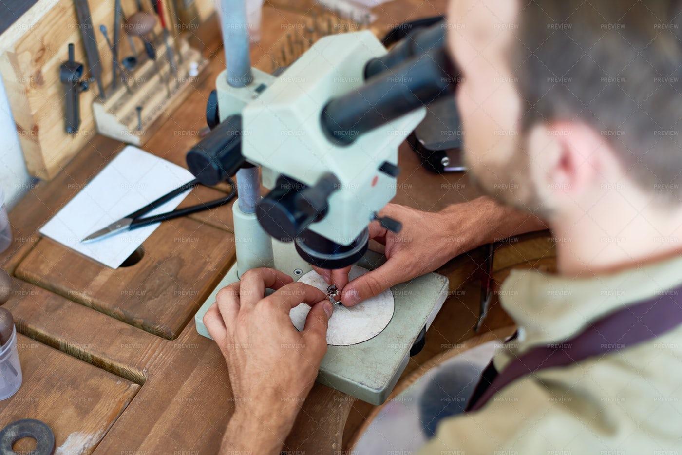 Jeweler Inspecting Precious Stone: Stock Photos