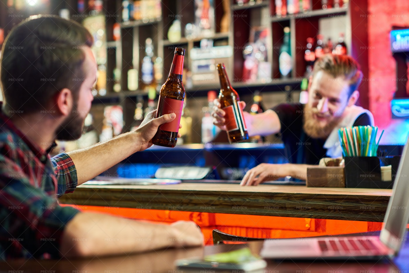 Man Clinking Beer Bottles With...: Stock Photos