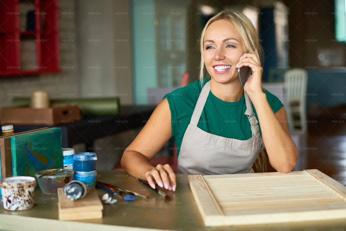 Female Artist Speaking By Phone In...: Stock Photos
