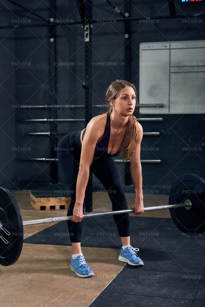 Young Woman Lifting  Barbell In Gym: Stock Photos