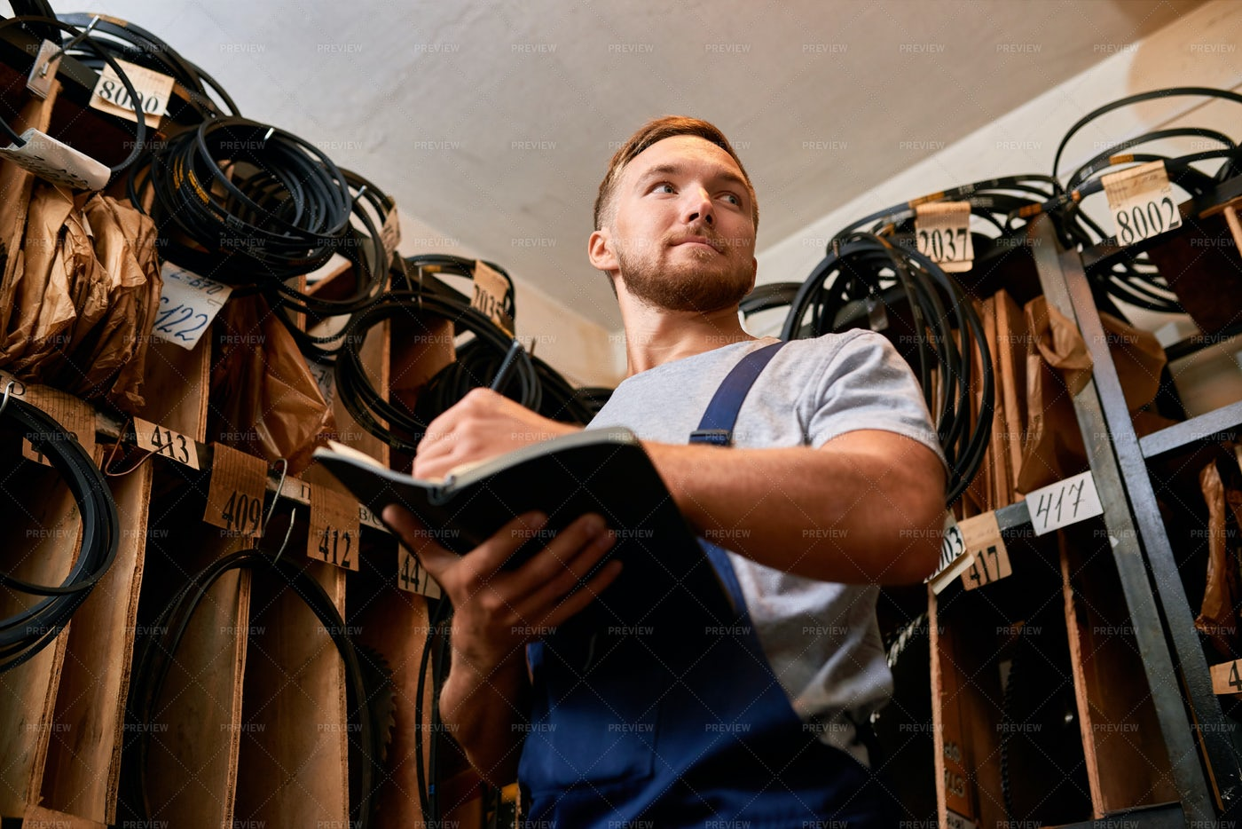 Mechanic Reviewing Stock In Storage...: Stock Photos