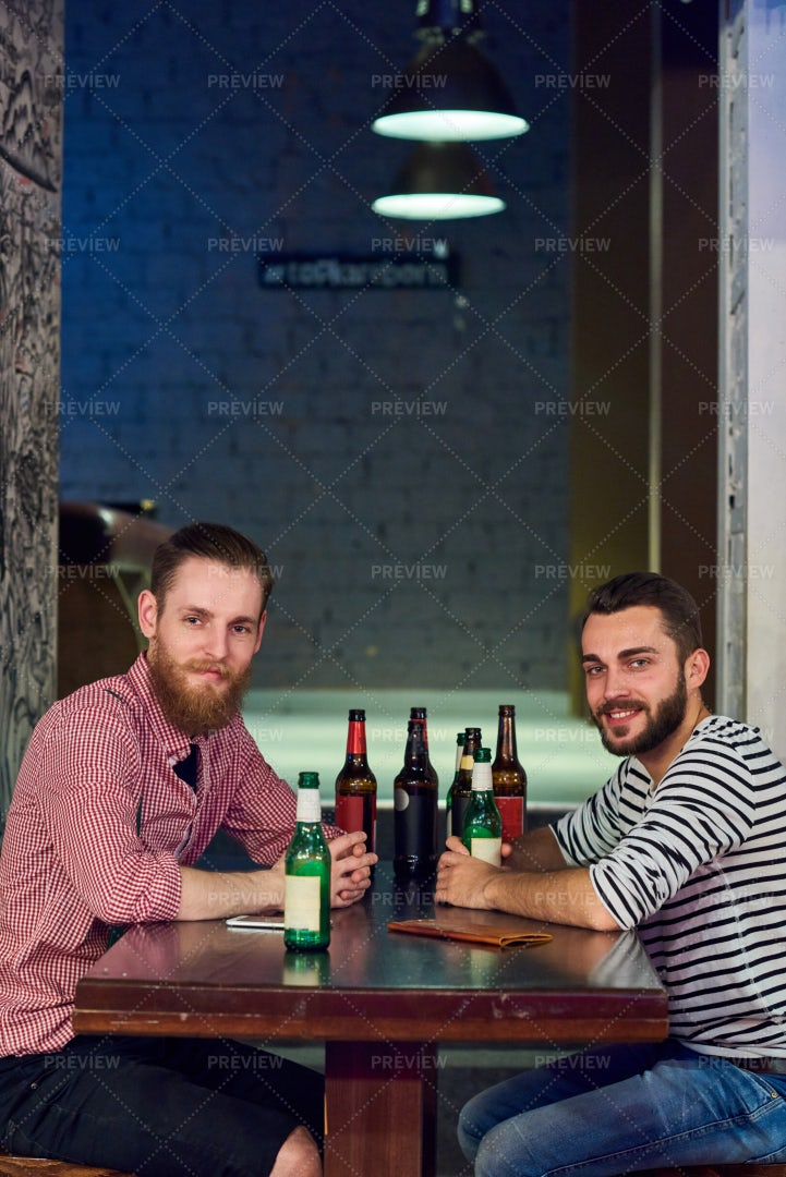 Two Buddies Drinking Beer In Bar: Stock Photos