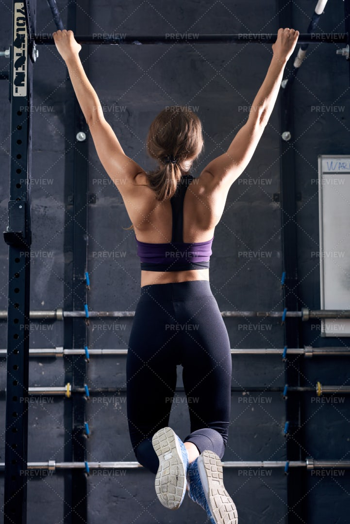 Young Woman Doing Pull Ups In Gym: Stock Photos