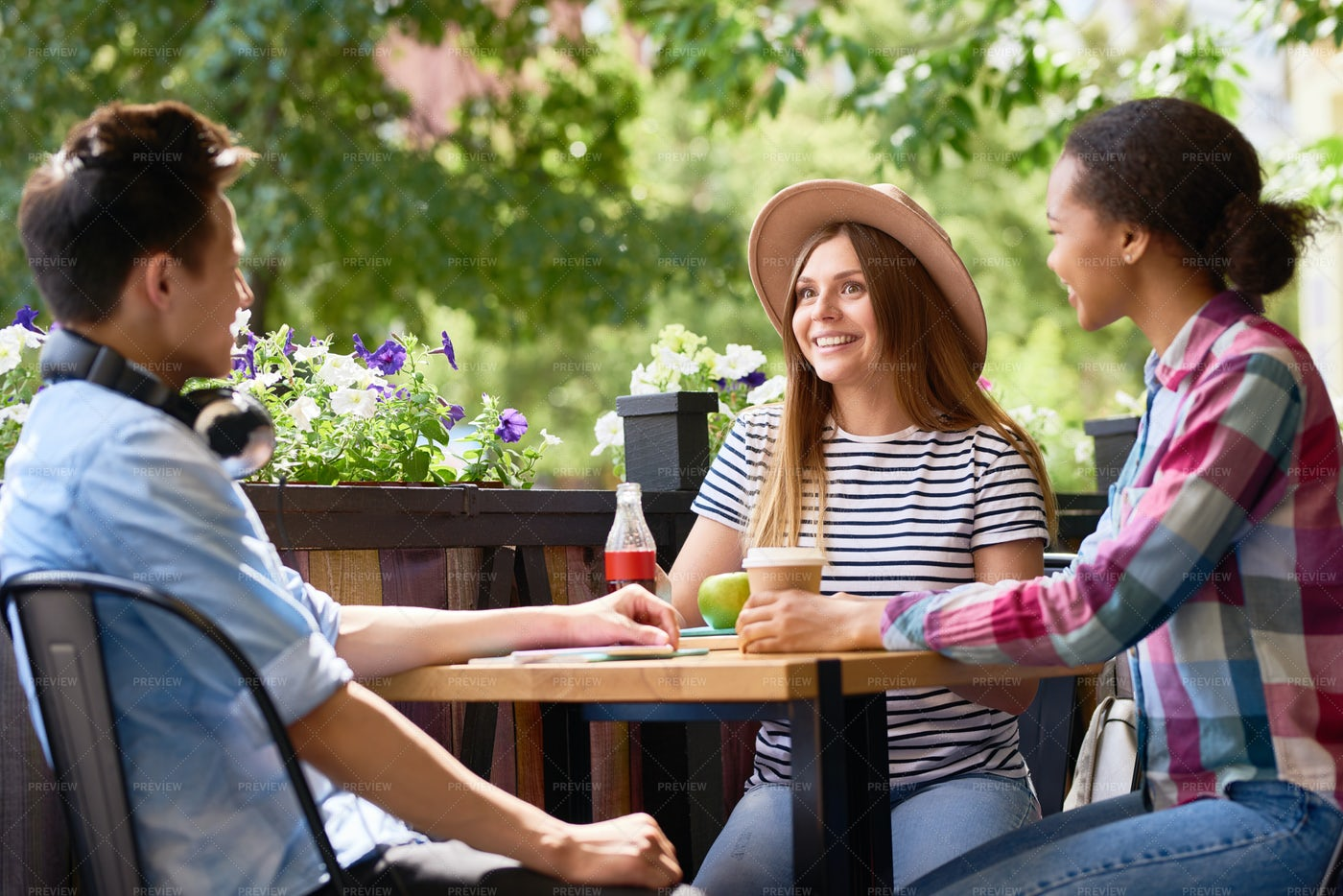 Young People Talking At Cafe Table: Stock Photos