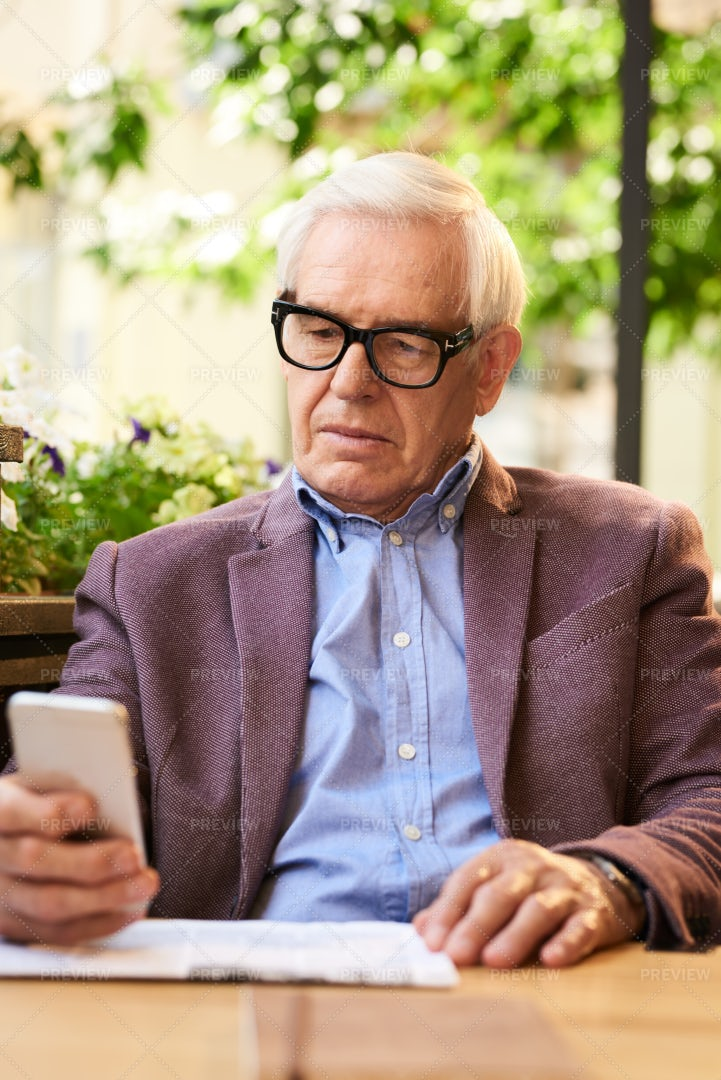 Senior Man Using Smartphone In Cafe: Stock Photos