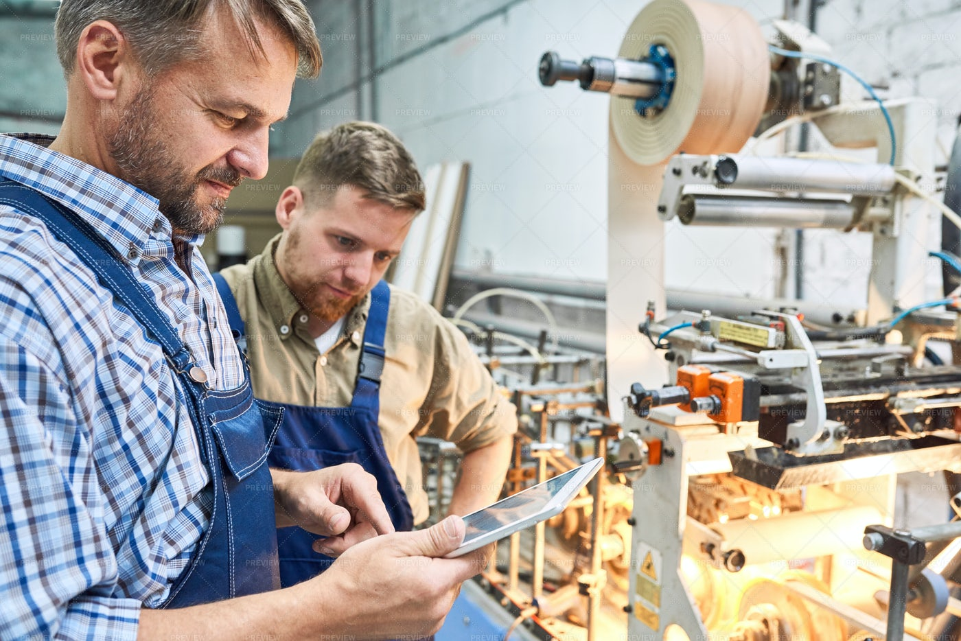 Workers Using Modern Machine At...: Stock Photos
