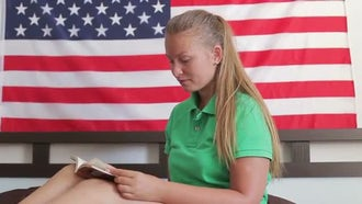 Girl Reading With American Flag: Stock Video