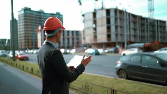 Engineer with Paper Plan Of A Building: Stock Video